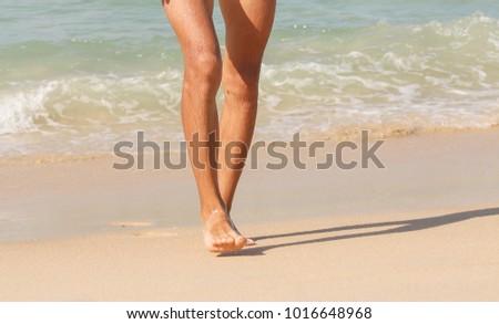 a man walks on the sand.  feet closeup. tropical beach. copy space. #1016648968