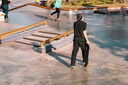 A man walks through concrete skate park with skateboard in his hand. Back view. Black style of clothes. Many obstacles, stairs, rails and shapes for skateboarding. City. Extreme sport. Public place