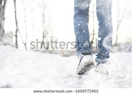 A man walks through the city on a snowy winter day.