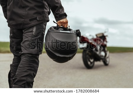 A man walks to his motorcycle, holding a helmet in his hands. Motorcycle helmet close up