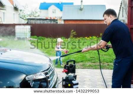 A man washes a black car with a high-pressure pump. With the help of a portable washing machine. Nearby is a child #1432299053