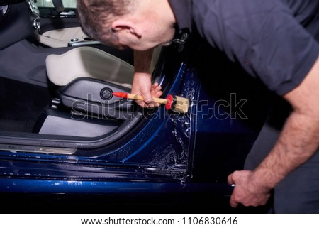 A man washes a blue car. Thorough washing of the body with foam and a high-pressure apparatus #1106830646