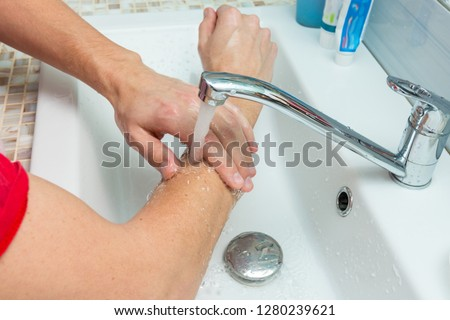 A man washes his hands up to the elbows under the tap
