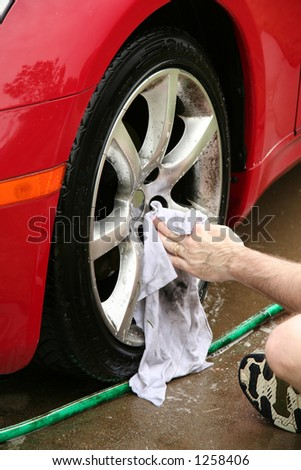 A man washing a wheel of a car.  There is slight motion blur on the hand as it washes.