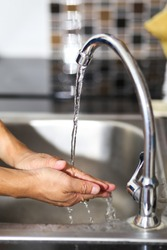 A man washing his hands at a faucet sink and water tab.
