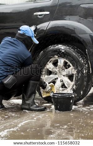 A man washing the car tire