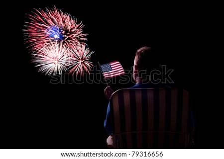 A man watches a fireworks show while waving an American flag. - stock photo