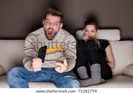 A man watching a game, while his girlfriend is sitting besides him bored. Showing the differences between the sexes.