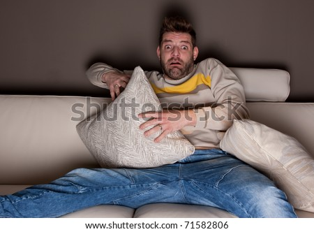 A man watching a horror movie. On the couch.