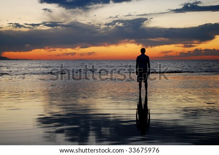 A man watching the sunset over a lake