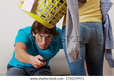 A man watching TV not wanting to clean with his wife