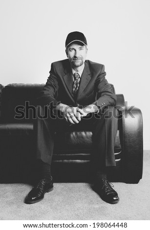 A man wearing a baseball hat sitting on a leather couch.