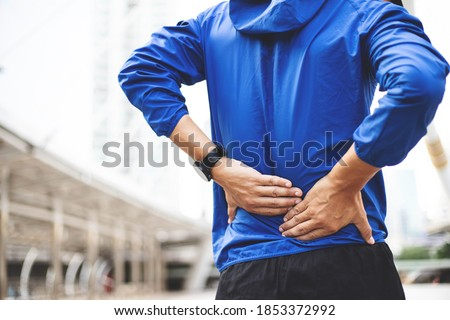 A man wearing a blue Windbreaker jacket., Back injury after exercise concept.It happens often in athletes practice overtain,Lifting heavy objects .In a Muscle inflammation concept. Сток-фото ©
