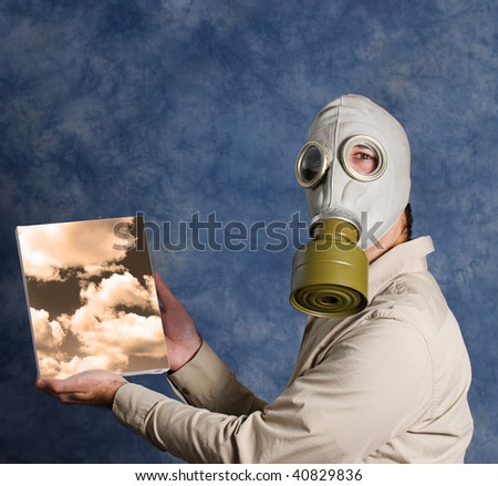 A man wearing a gas mask and holding a painting of a sky he painted