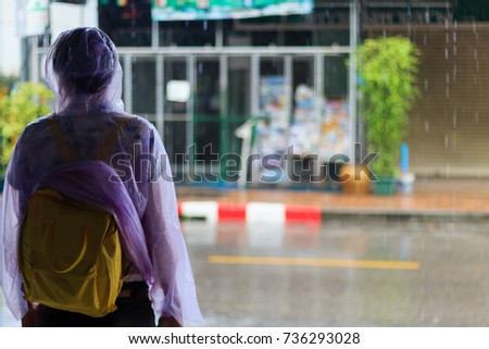 A man wearing a raincoat Shoulder bag yellow standing beside the road, sheltering heavy rain