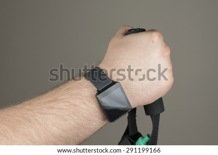 A man wearing a smart watch using a resistance band. #291199166