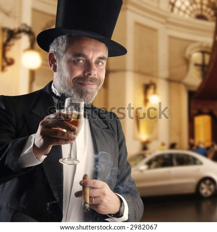 a man wearing a smoking holding a glass and cigar, against a luxury blurry background