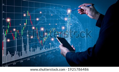 A man wearing a suit on his left hand holding a cell phone His right hand poked a pencil on a fast-growing stock chart. Globe background and blurred lights
