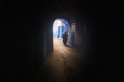 A man wearing a traditional Moroccan djellaba walks to the light through a dark tunnel and archway in Chefchaouen, Morocco.