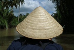 A man wearing a traditional Vietnamese hat on a water boat.
