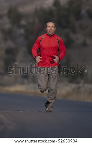 A man wearing athletic clothing is jogging down a road with a high desert landscape in the background. Vertical shot.