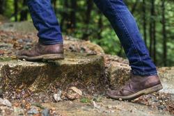 A man wearing brown chukka boots climbing up steps