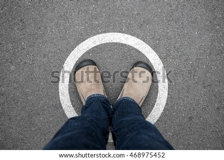 A man wearing brown suede shoes and blue jeans standing in white circle on asphalt concrete floor. Standing in boundary limit and never think different.