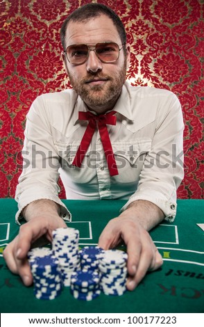 A man wearing glasses, a white shirt, and a red Texas tie sits at a blackjack table. He is making a big bet with all of his chips./Man Playing Blackjack Bets All His Money