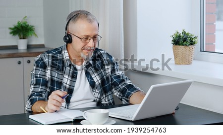 A man wearing headphones participates in online negotiations on a laptop.