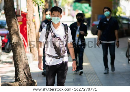 A man wearing mouth mask against air smog pollution PM 2.5 and Coronavirus at roadside in Bangkok, Thailand 2020.