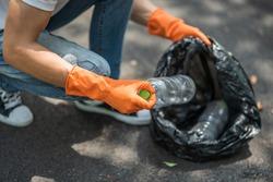 A man wearing orange gloves collecting garbage in a black bag. Selective focus.