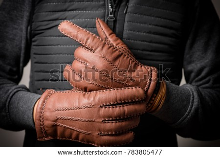 A man wearing the brown leather gloves in winter. Stock photo ©