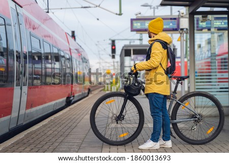 A man, wearing winter clothes, at the station, is about to get on the train, with his bicycle. stock photo