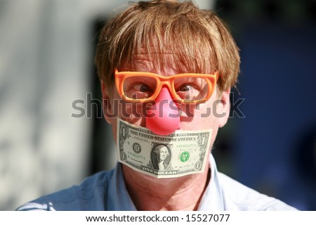 a man wears a rubber clown nose and glasses with a dollar bill taped over his mouth in protest against inflation and the rising cost of goods and services