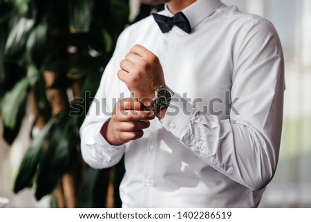 A man wears a watch on his hand #1402286519