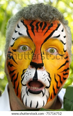 A man who has been painted to look like a tiger, acting surprised.