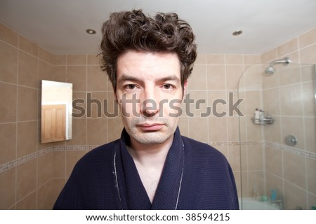 A man who has just woken up looks into the bathroom mirror.