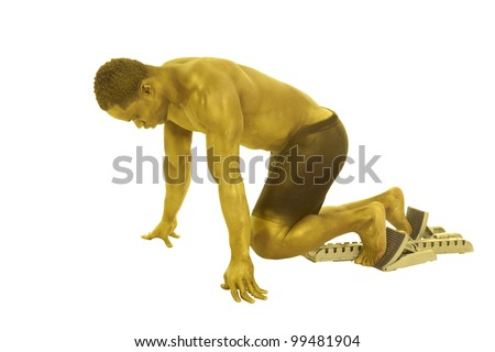A man who is painted gold with his feet on the running blocks ready to start the race,