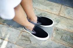 A man who is wearing black and white slip-on shoes that are comfortable for everyday wear.