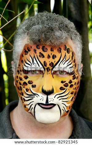 A man who\'s face is painted to look like a leopard.