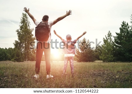 A man with a backpack, a father and his son on a hike, walking during walks in the woods. Family life, pastime with the family, the upbringing of children. #1120544222