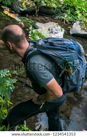 A man with a backpack is exploring alone the banks of a small river. Concept of exploration and survival in the wilderness.