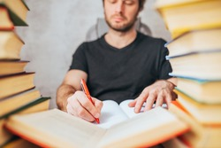 A man with a ballpoint pen writes in a notebook in a library surrounded by books - scientific work