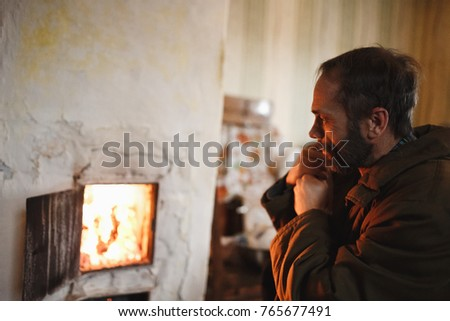 A man with a beard basking near village old Russian stove. Pensive old man. Dreams, looking at the fire in the fireplace. The life of the poor. An unhappy man. Sadness and sorrow. Depression.