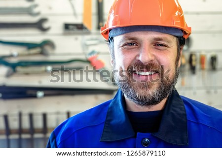 A man with a beard in a helmet and work clothes is smiling a snow-white smile against the background of a stand with tools. Portrait of a worker in workwear with copy space.