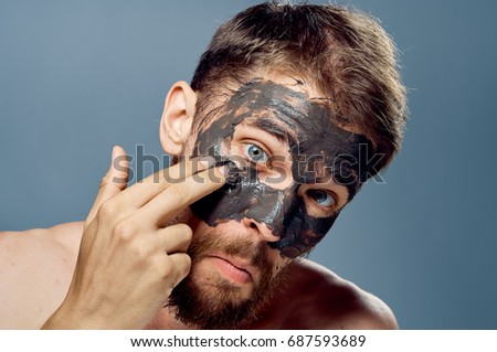 A man with a beard on a gray background applies clay cosmetic face mask, beauty, health. #687593689