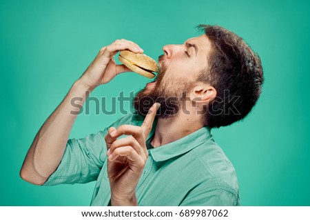 a man with a beard on a green background holding a hamburger, unhealthy food.