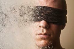 A man with a blindfold over his eyes disintegrates into dust.