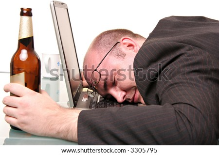 A man with a bottle of beer fallen to sleep on his computer. Isolated on white