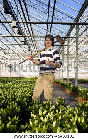 A man with a broom in his hand giving a thumbs-up inside a glasshouse, surrounded by potted plants